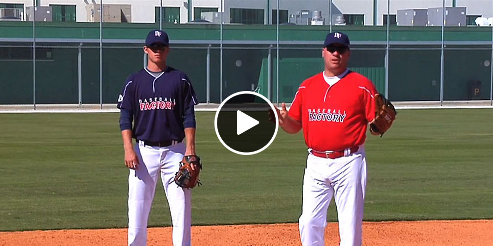 coach and player standing on the mound
